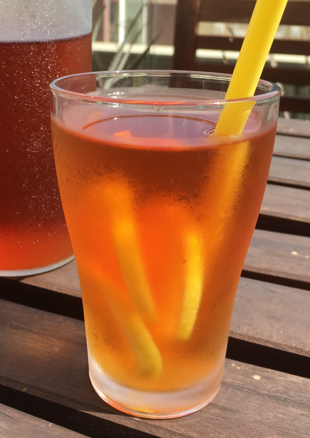 A glass of Cold Brewed Tea with lemon slices and a straw