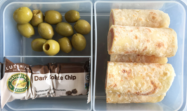 A lunch box containing olives, a granola bar, and wraps using Soft Gluten-Free Tortilla Flatbread