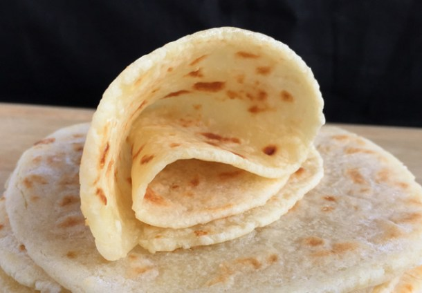 A rolled up Soft Gluten-Free Tortilla Flatbread on a stack of flatbread