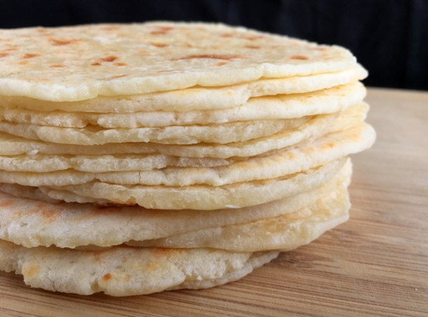 A stack of Soft Gluten-Free Tortilla Flatbread on a wooden cutting board