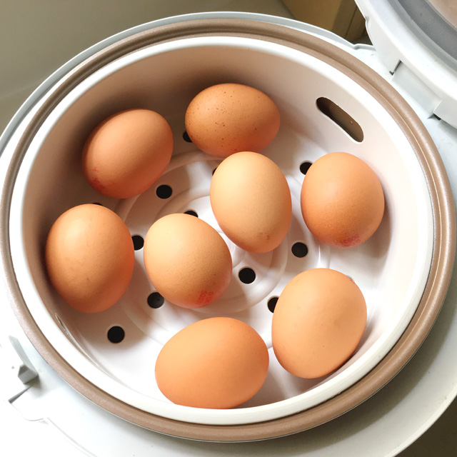 Eight brown eggs in a white steamer basket in a rice cooker