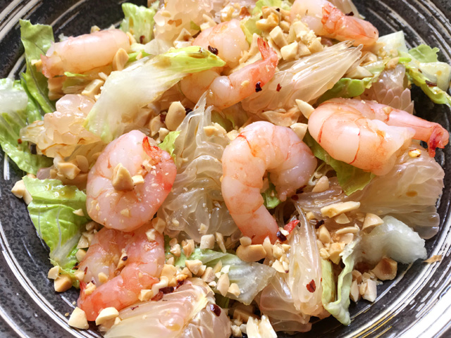 A stone bowl containing lettuce, pomelo wedges, shrimp, and chopped peanuts
