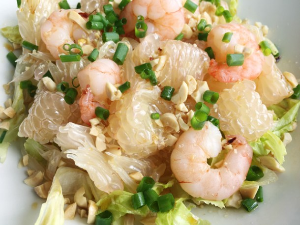 A bowl of Prawn Pomelo Salad containing pomelo wedges, lettuce, shrimp, chopped peanuts, and chopped green onion