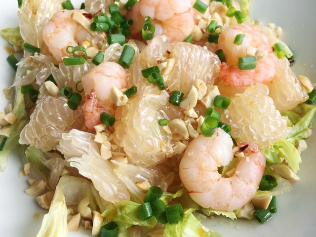 A white bowl containing pomelo wedges, lettuce, shrimp, chopped peanuts, and chopped green onion