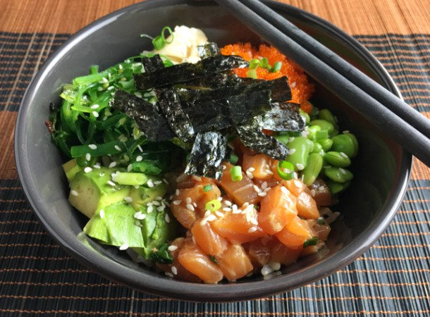A grey dish of salmon poke bowl with avocado, beans, seaweed, tobiko, and ginger with chopsticks