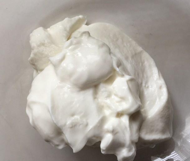 A glass bowl containing white Greek yogurt for creamy cucumber tzatziki
