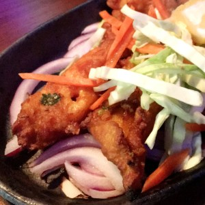 Deep-fried breaded fish with carrots, cabbage, and onions at Hungry Eye Restaurant