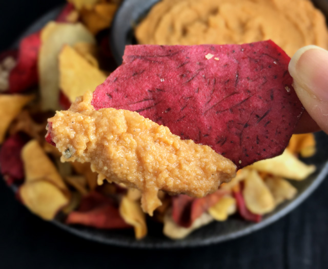 Close-up of a red root chip scooped in Roasted Cauliflower Hummus with tomato paste.