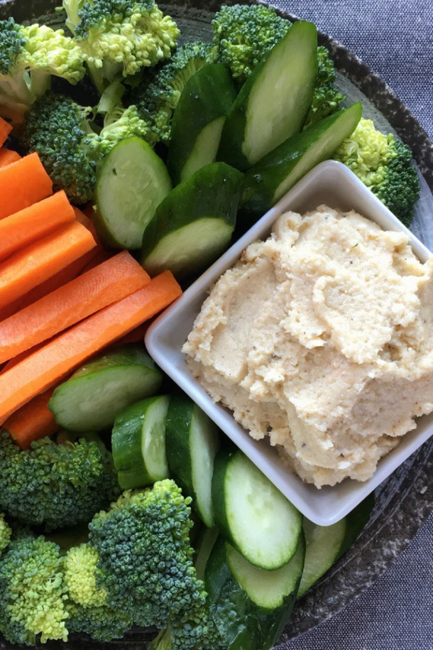A white square dish containing Roasted Caulflower Hummus, on a round plate with raw cucumber slices, broccoli, and carrot sticks.