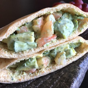 Two shrimp avocado tzatziki pockets on a black plate