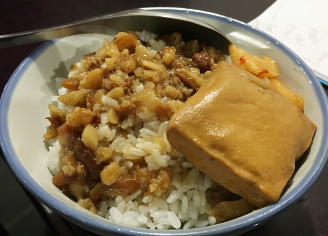 A bowl of braised ground pork over rice and a square of tofu - eat in Taipei