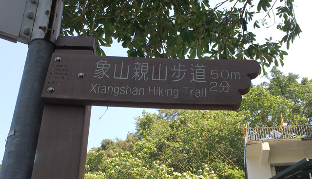 A wooden marker sign indicating direction and distance to Elephant Hill in Taipei
