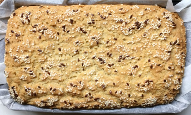 Top overhead photo of a golden brown Soft Homemade Gluten_Free Bread, topped with sesame seeds and whole flax seeds