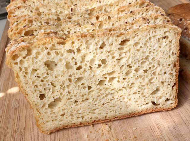 A wooden cutting board with a slice of Soft Homemade Gluten-Free Bread with lots of air bubbles
