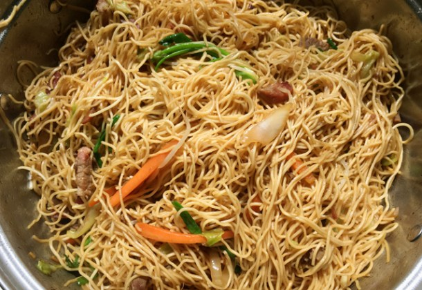 A stainless steel wok containing BBQ pork chow mein with carrots, onions, green onions