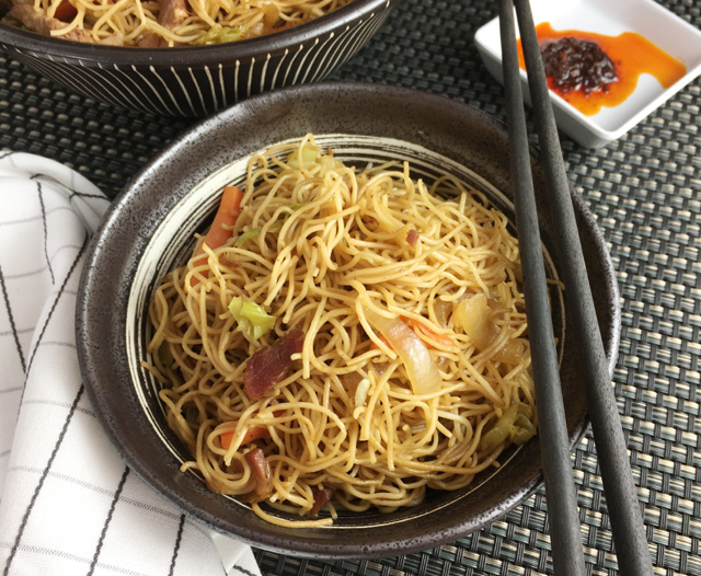 A pair of black chopsticks resting on a bowl containing noodles, onions, BBQ pork, and carrots
