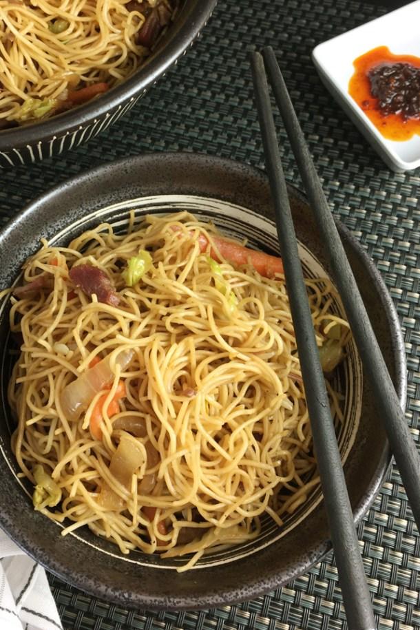 A pair of black chopsticks resting on a bowl of BBQ pork chow mein