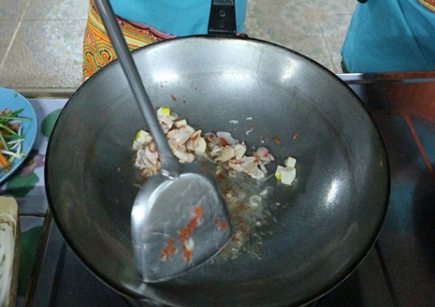 Chicken, onions, tofu and chili peppers being cooked in a large silver wok with a stainless steel spatula in Chiang Mai