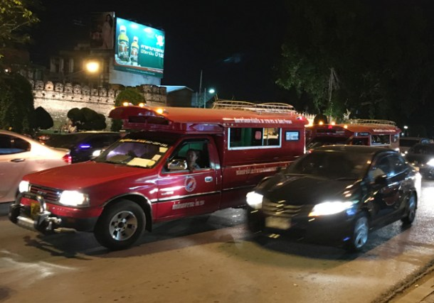A street view showing red trucks in traffic in Chiang Mai