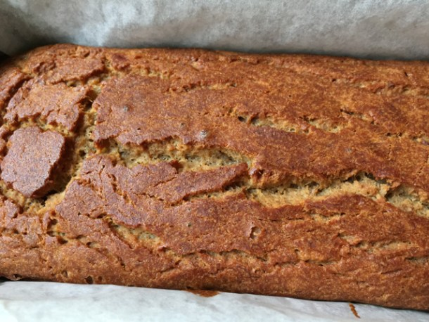Close-up of fresh-baked gluten-free banana bread in a parchment paper lined loaf pan