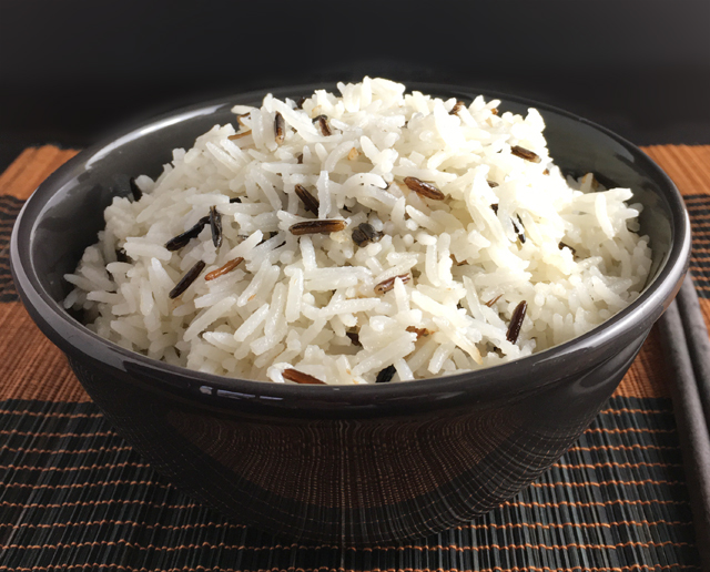 Closeup of a dark bowl containing coconut rice made from white basmati and black wild rices