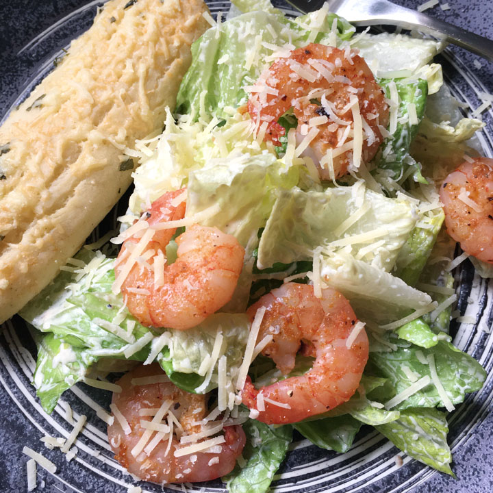 A dark round plate containing green salad with grated parmesan cheese, pink shrimp, and a breadstick