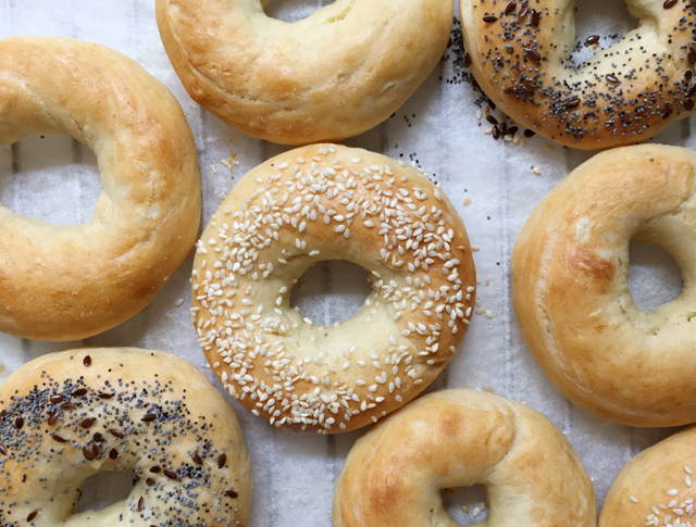 Plain, sesame, and poppyseed topped homemade bagels on white parchment paper