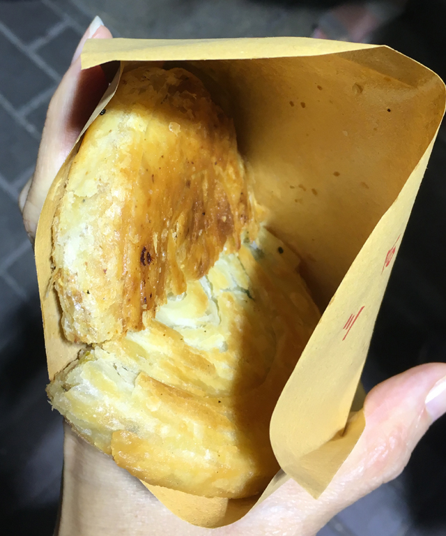 Two Sichuan pancake halves in a paper bag on a Hong Kong foodie tour