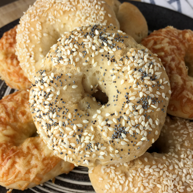A bagel topped with sesame seeds and poppy seeds, on top of a pile of gluten-free bagelss on a plate