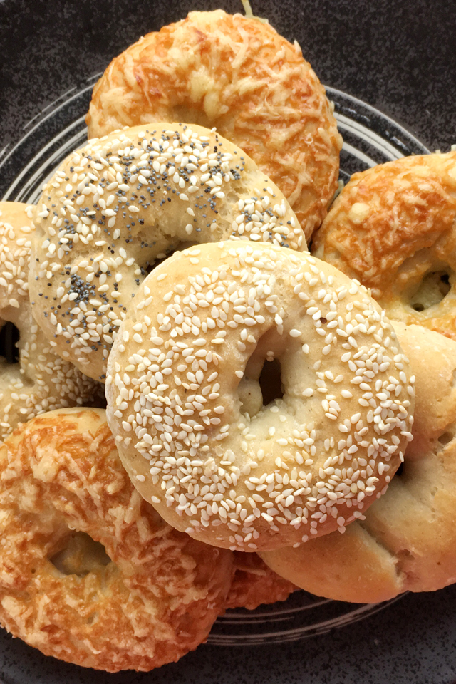 A pile of baked gluten-free bagels, topped with sesame seeds, poppyseeds, and cheese