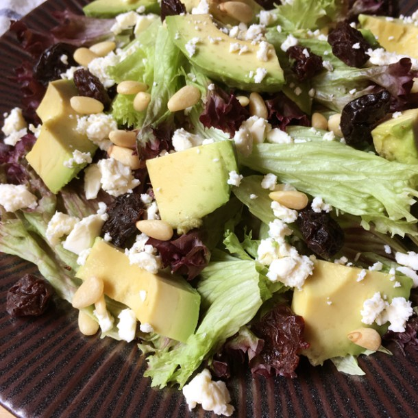 Close-up of avocado feta salad with dried cherries, pine nuts, and leaf lettuce
