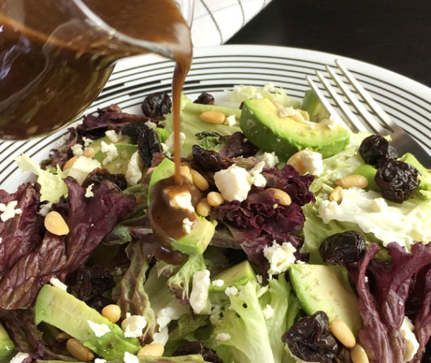 Balsamic vinaigrette being poured over a salad of avocado, feta, pine nuts, and lettuce greens