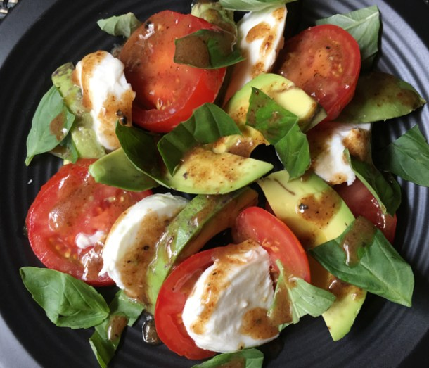 A black plate containing sliced tomatoes, white mozzarella cheese, avocado chunks, and basil leaves, drizzled with balsamic vinaigrette