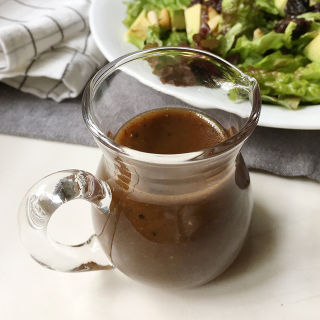 A glass pitcher containing brown balsamic vinaigrette, a plate of salad in the background