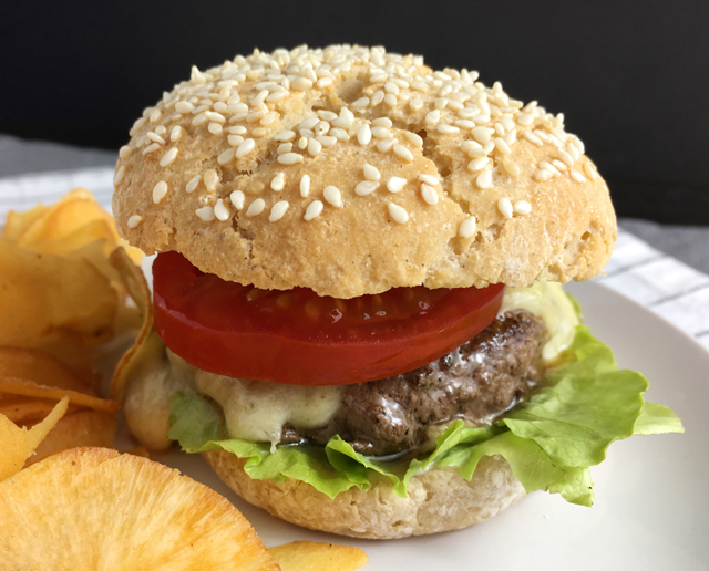 A hamburger patty with melted cheese, a slice of red tomato, and green lettuce in a gluten-free bun on a white plate