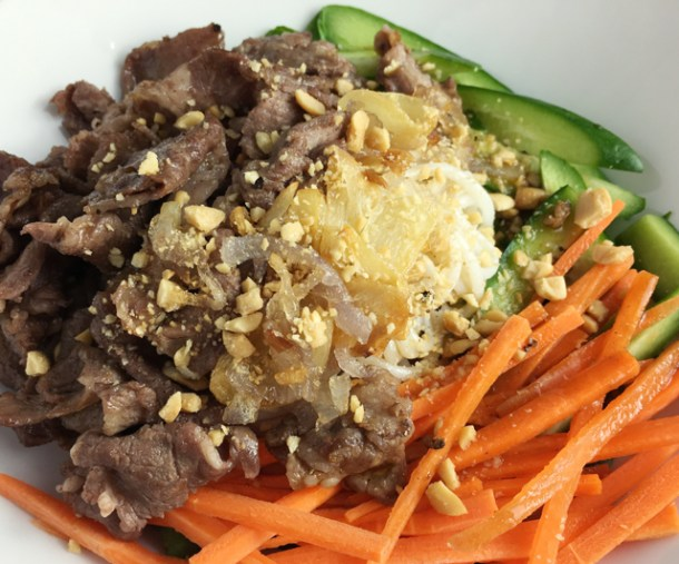 A white dish containing Savory Vietnamese Beef Vermicelli containing white rice noodles, vegetables, garlic and shallots