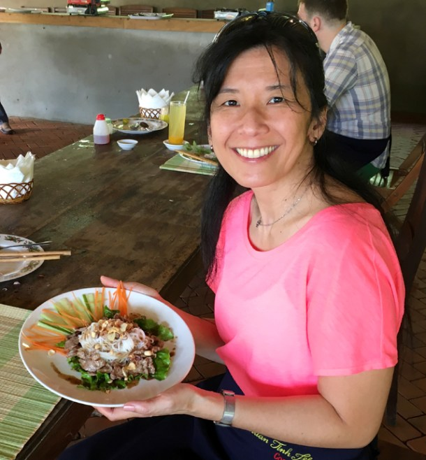 An Asian woman holding a white round plate containing beef, white rice noodles, lettuce, carrots, and cucumber