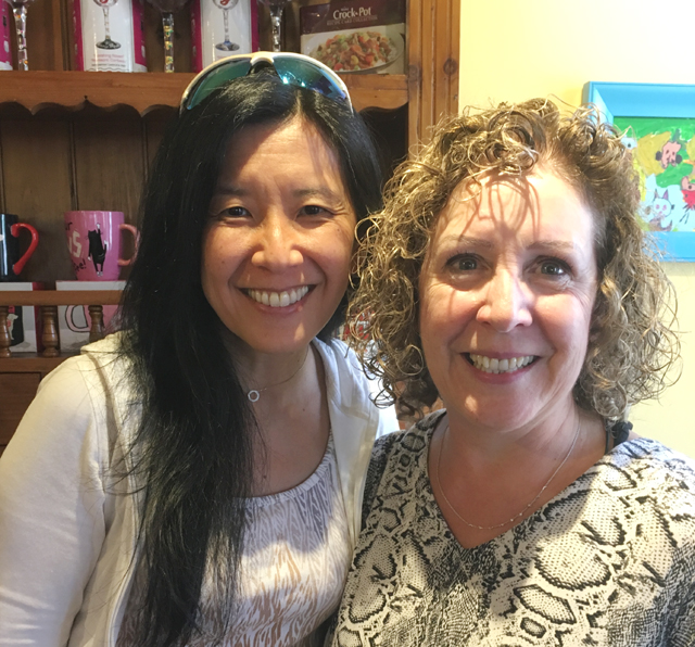An Asian and a Caucasian woman, meeting food bloggers