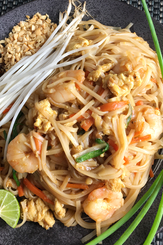 A dark plate containing shirmp pad thai, white bean sprouts, crushed peanuts, and a lime wedge