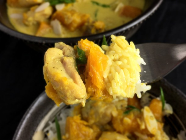 A fork containing rice, chicken, and pumpkin for a bowl of chicken pumpkin curry
