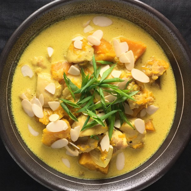 A dark metal bowl containing yellow chicken pumpkin curry topped with sliced almonds and green onions