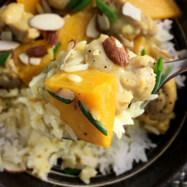 Closeup of a spoon containing an orange pumpkin chunk rice, a piece of chicken and chopped green onions