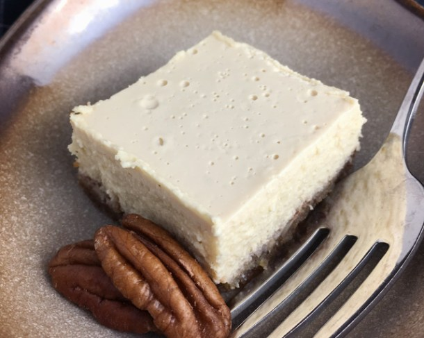 One cheesecake square and two pecan halves in a brown dish with a fork