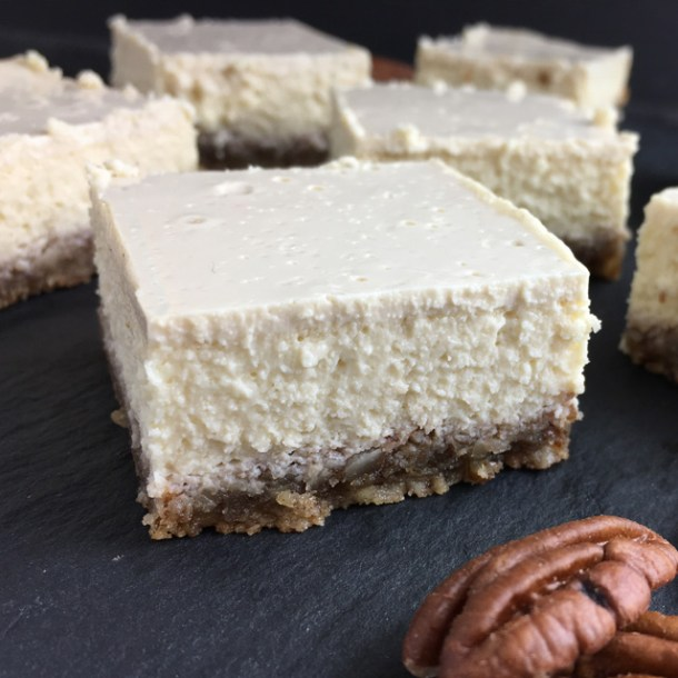 Six white cheesecake squares and pecan nuts on a grey stone surface