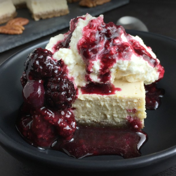 A cheesecake square topped with whipped cream and reddish fruit sauce in a black dish