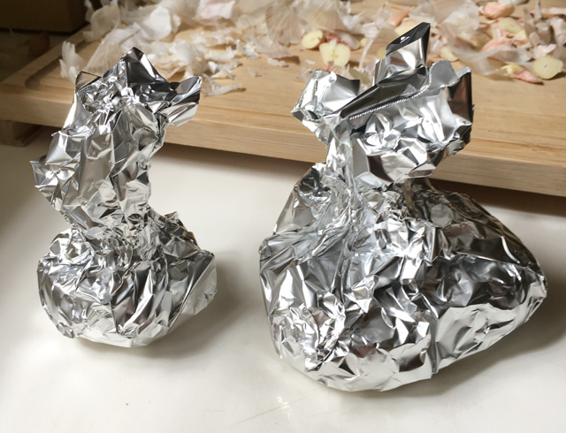 Two silver foil bundles containing garlic for roasted garlic