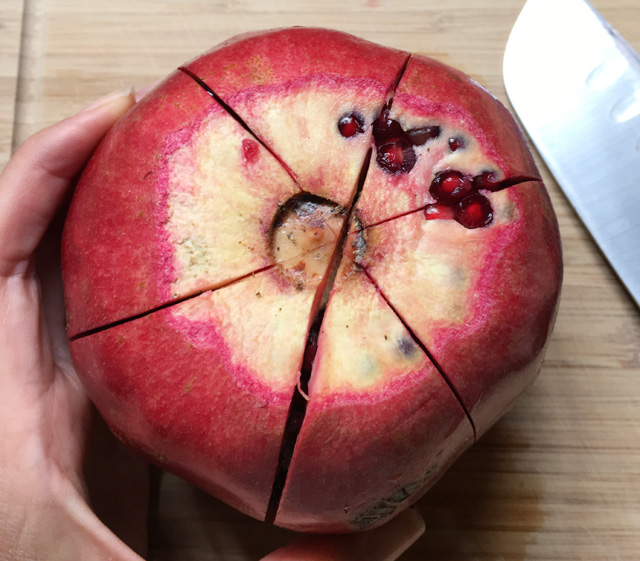 A red pomegranate with cuts made into the skin