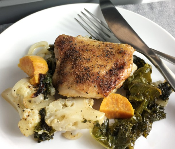 A fork and knife resting on a white round plate containing roast chicken and kale and cauliflower and sweet potatoes