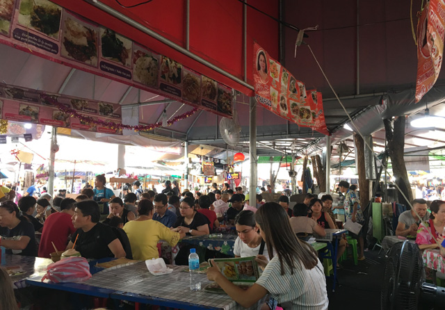 A crowded area of people sitting at tables to eat