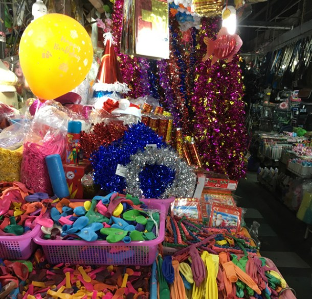 Different colored shiny Christmas garland and baskets of balloons